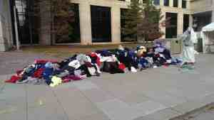 A waist-high pile of clothing about 20 feet long, on a sidewalk.