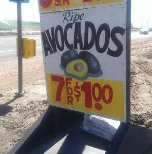 painted sign offering avocados, 7 for $1