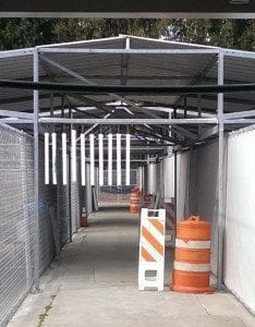 traffic barrels and barricades, and a series of PVC pipes hanging vertically from the ceiling