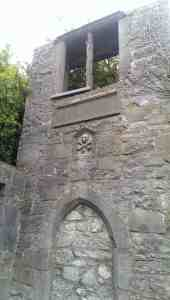 window in stone wall with skull and crossbones