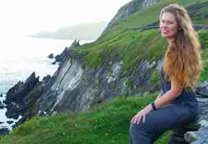 Laura sitting, blonde hair over shoulder, before rocky cliff with surf crashing below