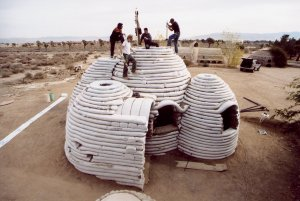 An image of workers standing atop a SuperAdobe building.