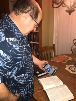 Photo of a man looking at new study bible and scanning QR code with smart phone