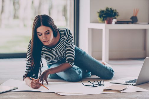 Concentrated on work. Confident young beautiful woman drawing something on blueprint while sitting on the floor at home