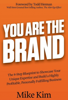 Image of Book Cover. Orange Background. White text reads: You Are the Brand. Black subtext reads:  The 8-Step Blueprint to Showcase Your Unique Expertise and Build a Highly Profitable, Personally Fulfilling Business. Written by Mike Kim.