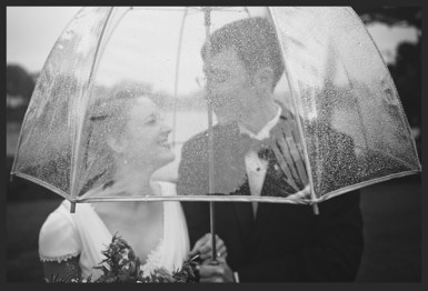 Happy couple with umbrella. Rainy and happy wedding.