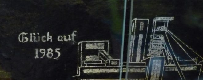 """Glück auf!"" engraved in white on a black stone. Miners pre-shift greeting and mine shaft."