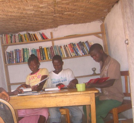 young people reading at a table with bookcase
