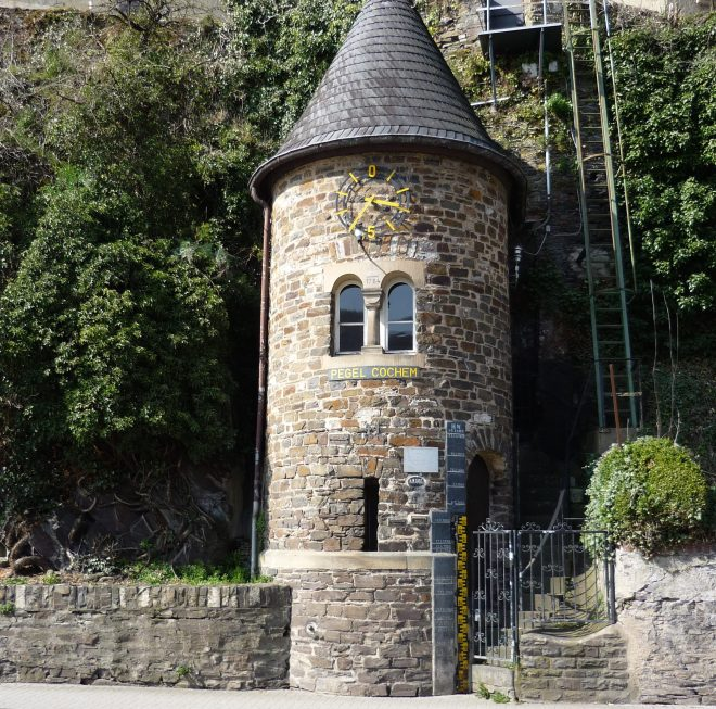 castle with towers and rooks, blooming pink cherry trees, tower with windows and door that make a funny, surprised face, Mosel river valley