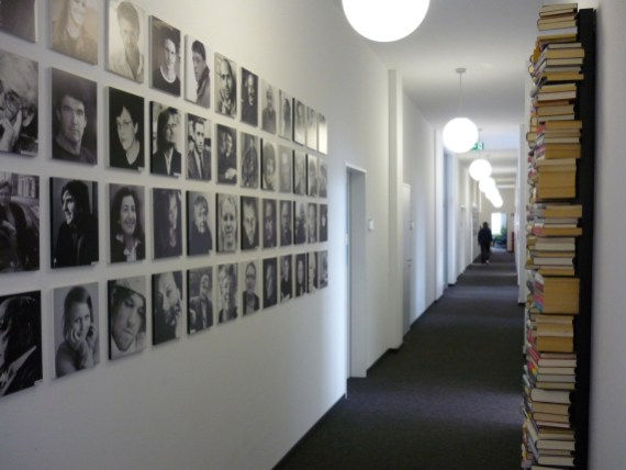 hallway with square portraits lined up in a grid 4 high by more than 10 across