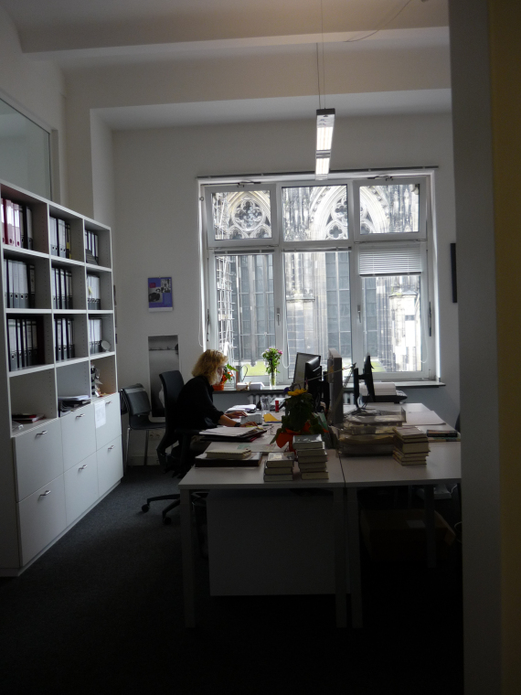 office with Cologne Cathedral visible through the window.