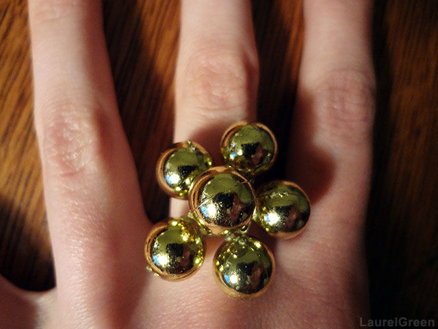 a photo of a hand with a ring with golden baubles on it