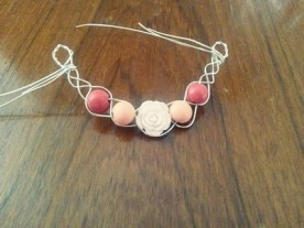 braided silver necklace piece with roses and pink beads