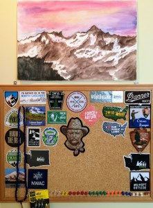My bulletin board is home to stickers and patches I've picked up here and there. Above it, the painting of the North Cascades is by my daughter, The Artist.