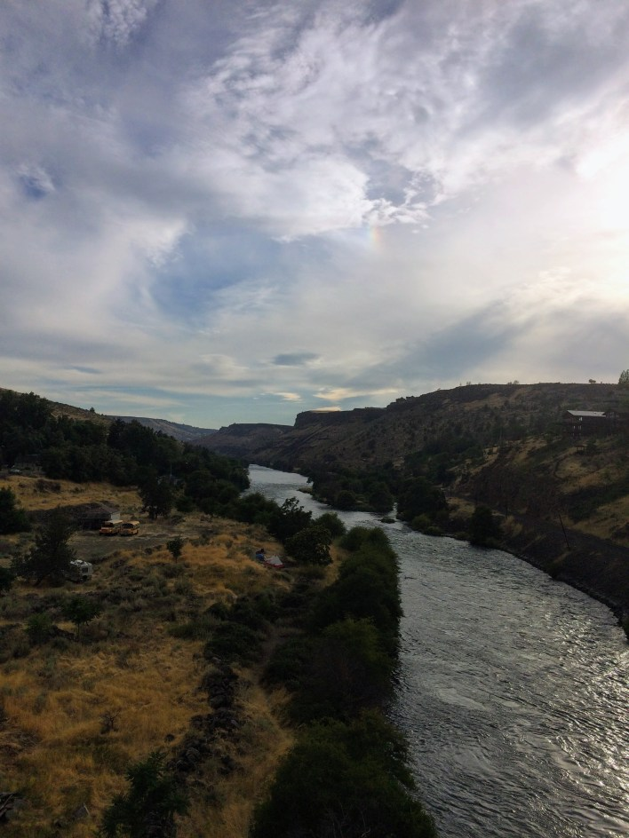 The Deschutes River flows through Maupin, Oregon, under cloudy, smoky evening skies.