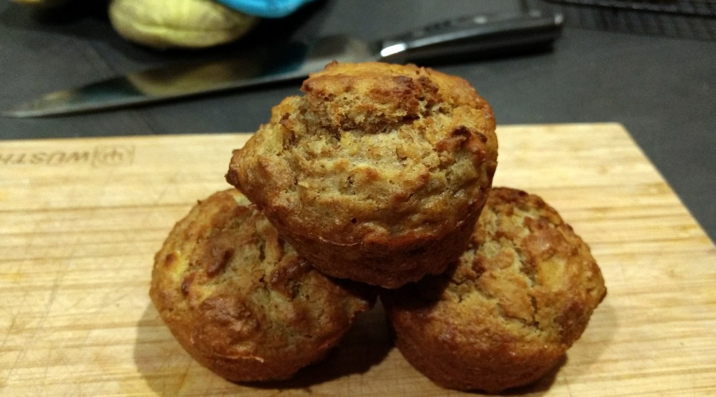 Three banana bran muffins stacked on top of a wooden cutting board
