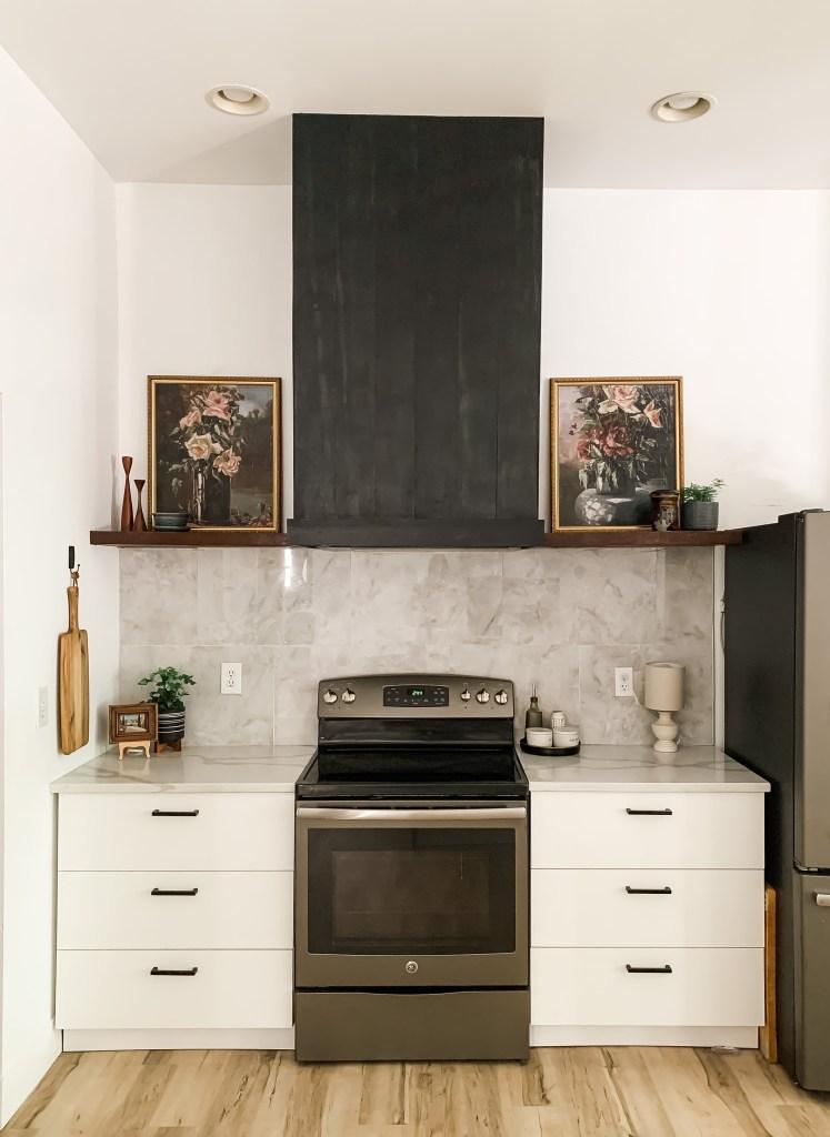 kitchen renovation with diy black vertical shiplap vent hood and wood floating shelves, marble look tile backsplash, white ikea cabinets, vintage floral art on shelves, wooden cutting board