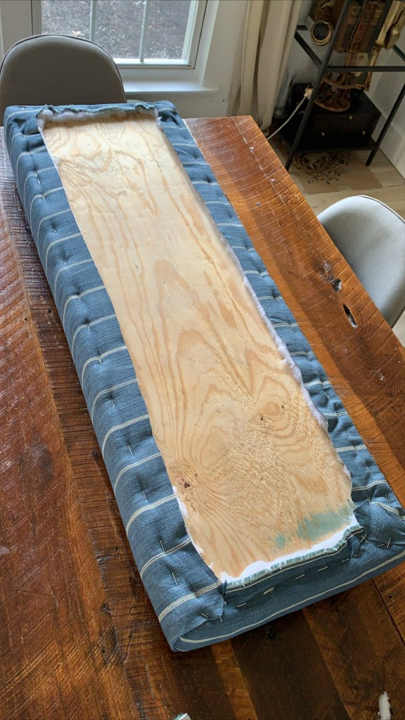 fabric stapled to based of bench seat cushion