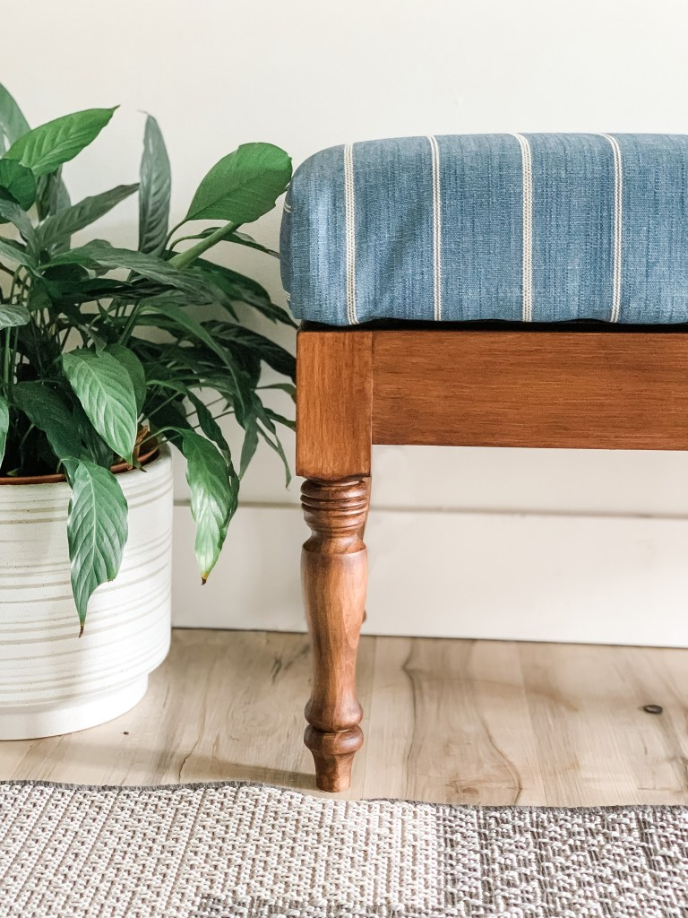 blue striped fabric upholstered bench with wood base, plant in ceramic planter