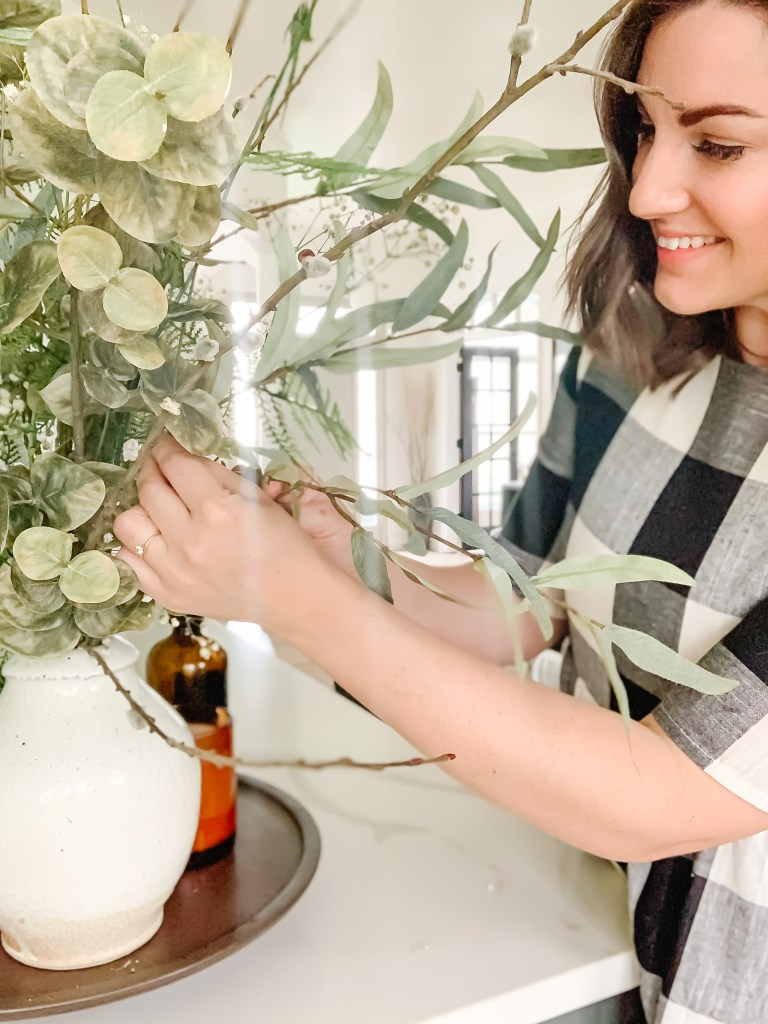 How To Style Faux Flowers + Stems. Brunette in black and white plaid dress arranging mixture of faux and real stems.