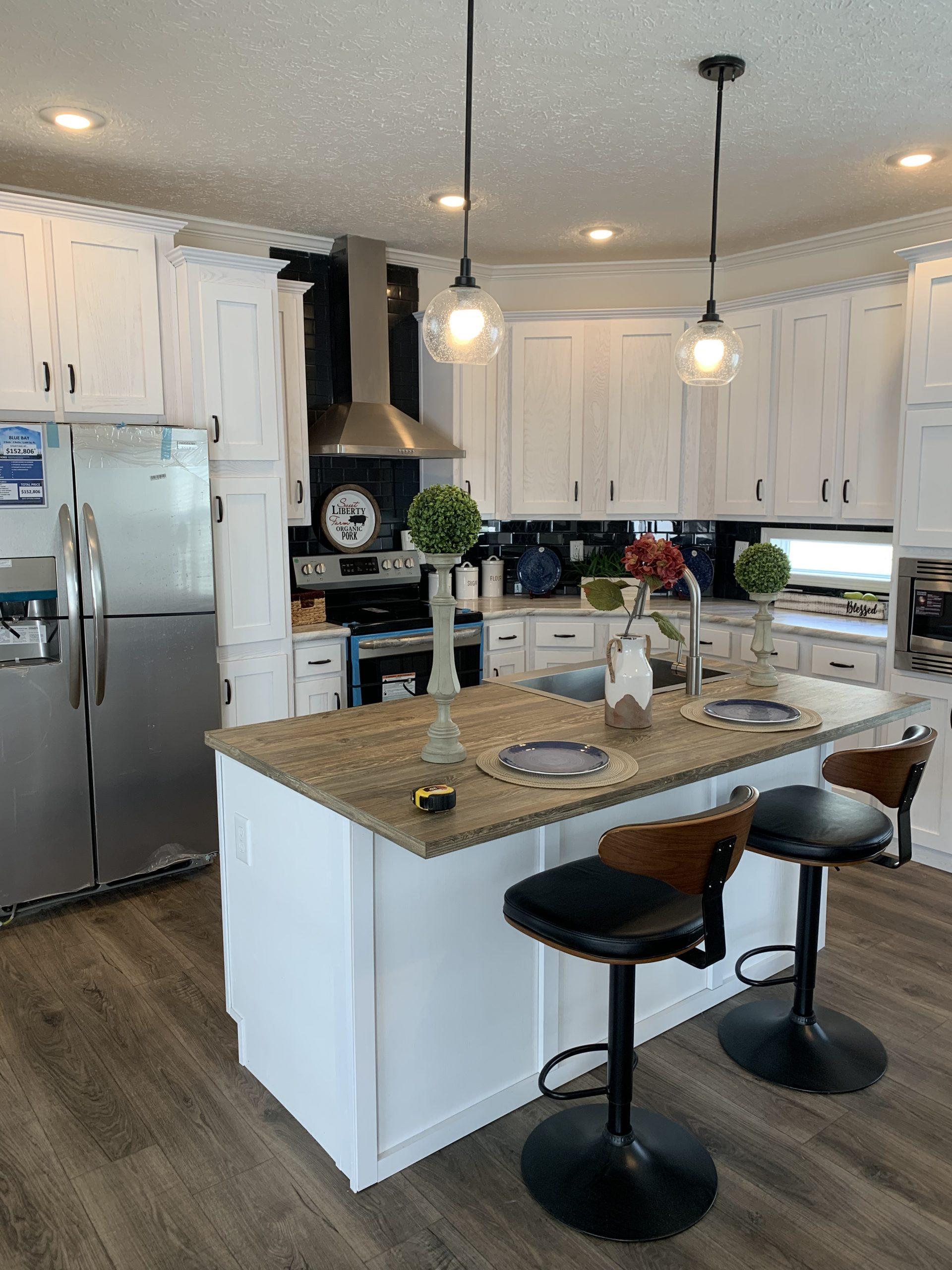 model home kitchen with White Island, barstools, stainless steel range chimney hood, tile backsplash, white kitchen basinets.
