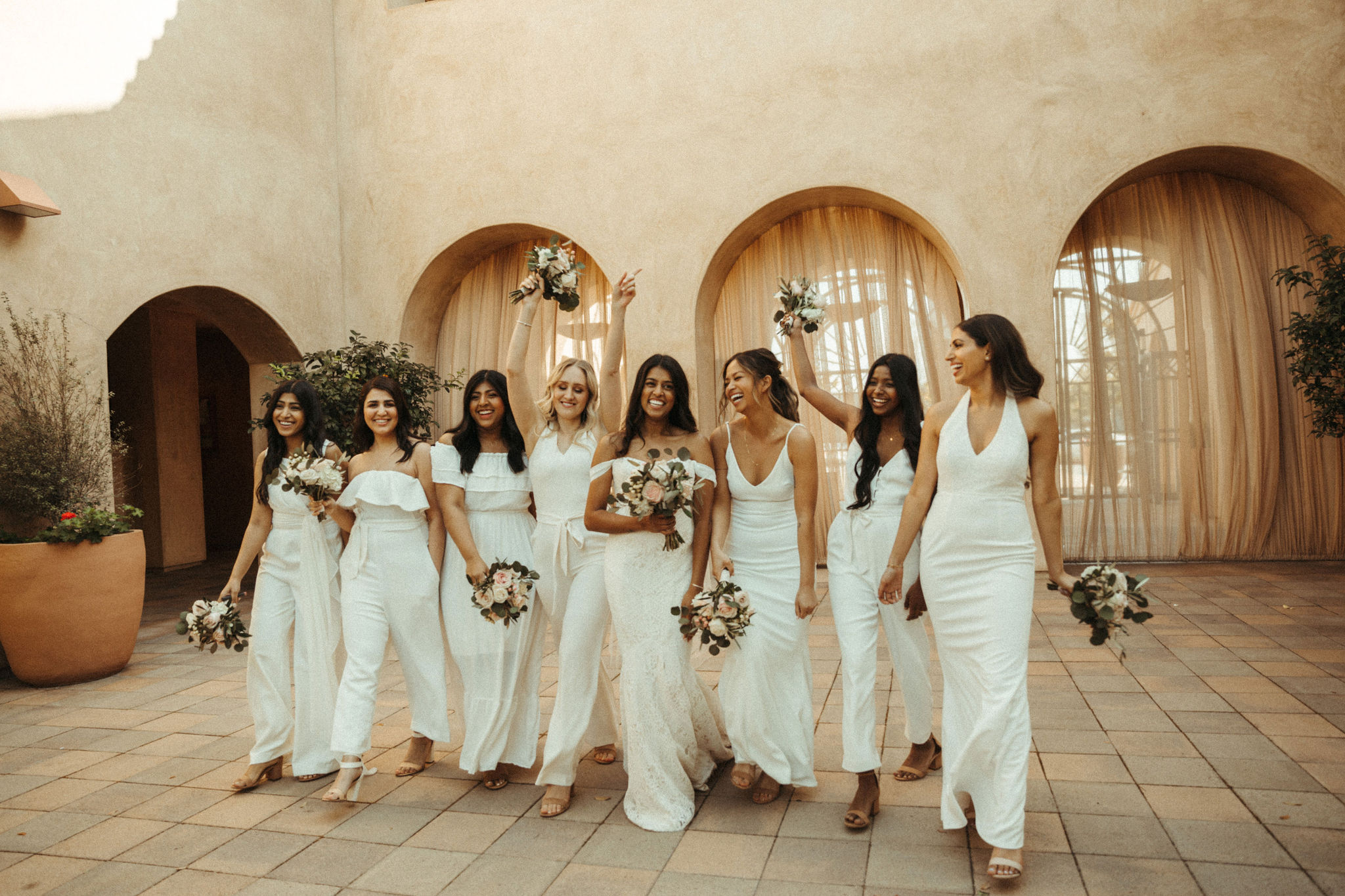 bridesmaids wearing all white jumpsuits and dresses
