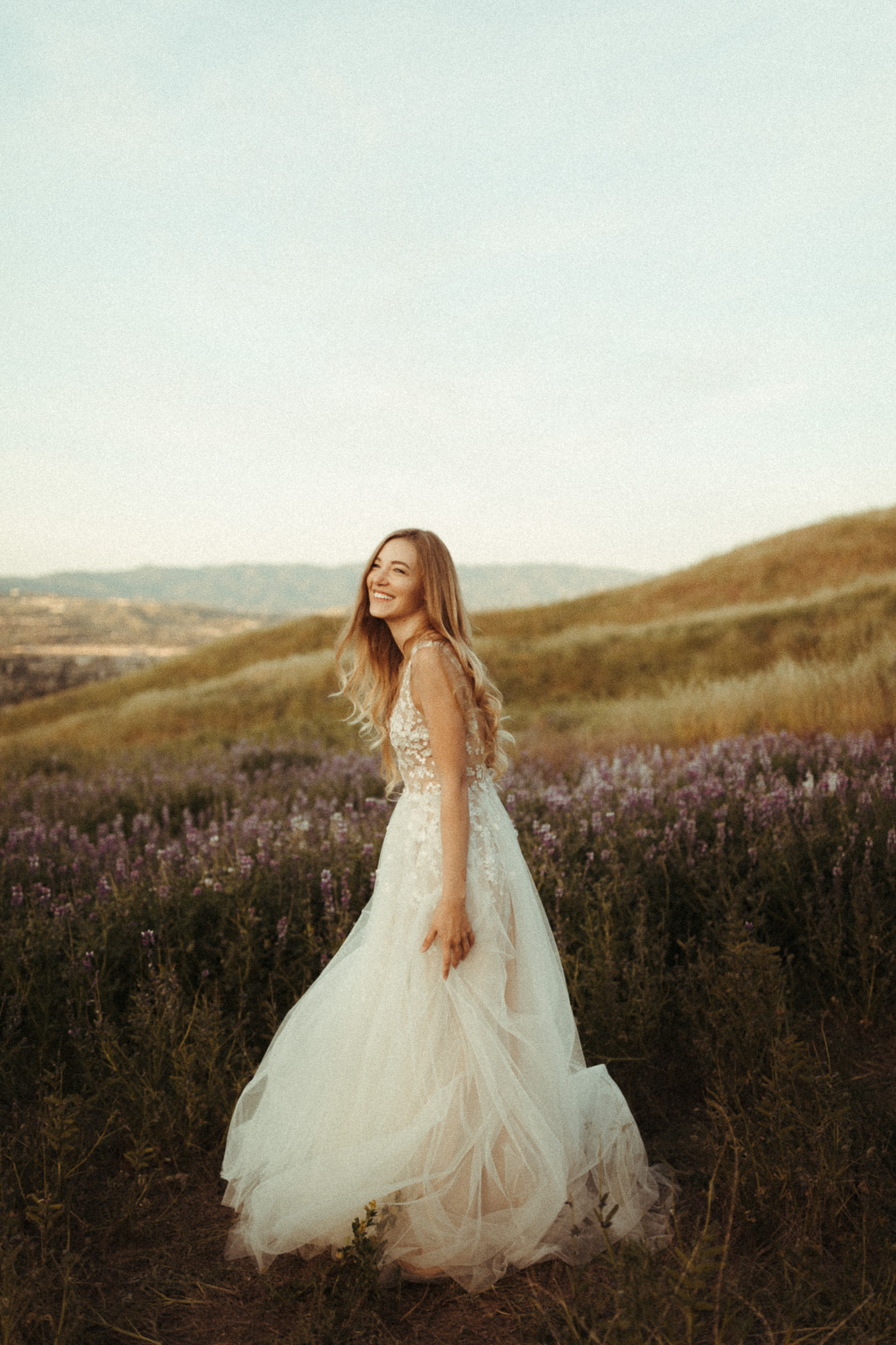 natural candid bride running around in her wedding dress in some lupine fields
