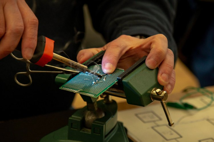 Close up of an attendee placing their hot soldering iron tip at the base of the forceps, clamped to their circuit board, while solder smoke billows up towards them.