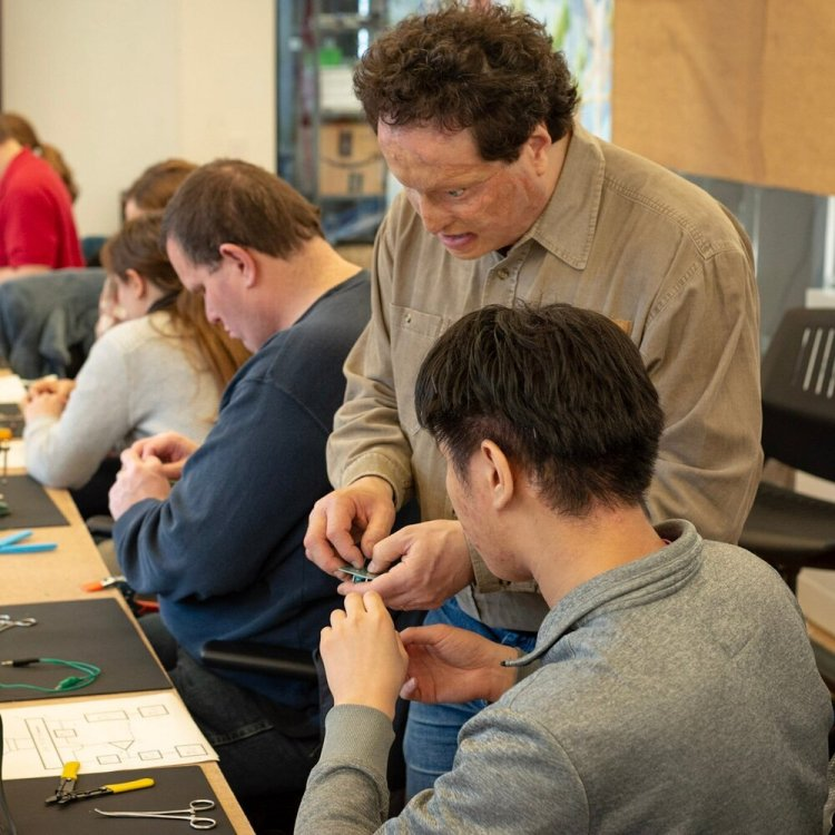 Six attendees sit at a long conference table at a blind soldering workshop, set up with individual soldering stations that include soldering mats, fans, helping hands, tools, a tactile schematic, and soldering irons. In the foreground, Josh Miele hands a circuit board to an attendee.