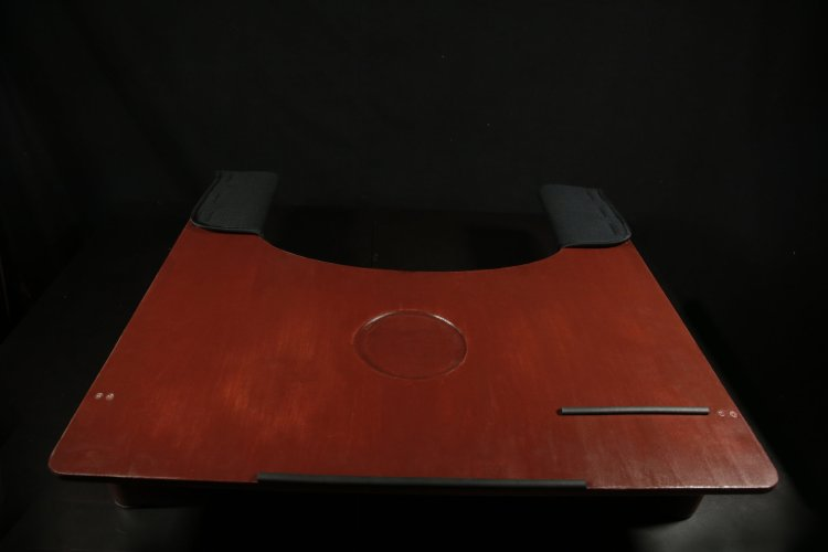 Front view of assistive workstation bed desk, with elbow padding and grip for holding pencils and a laptop