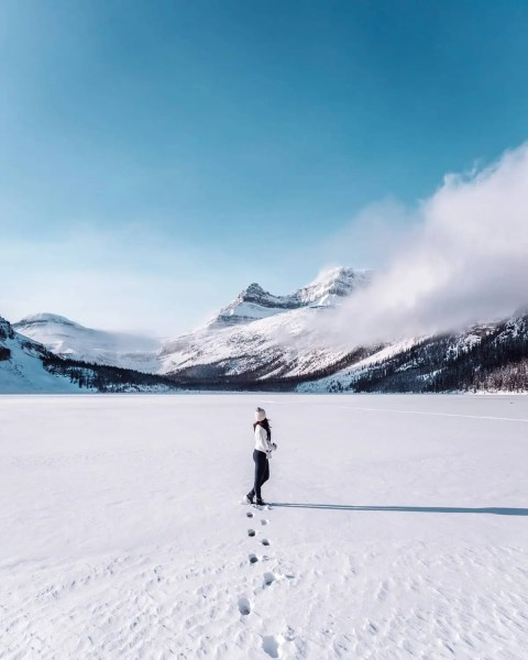 Bow Lake, Alberta frozen with snow, sunny with low cloud