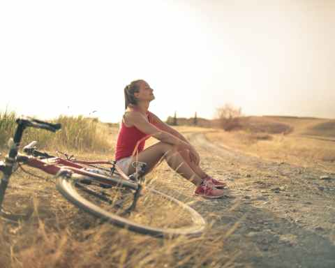 sportive woman with bicycle resting on countryside road in sunlight