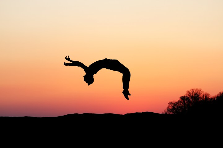 silhouette of gymnast doing a backflip in sunset