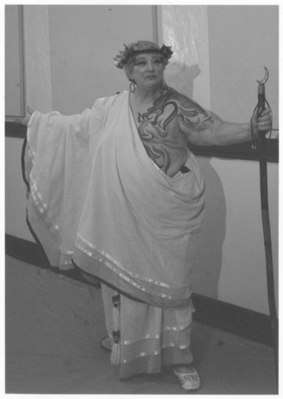 Woman in Greek robe costume with her right side bare with her mastectomy scar painted  with a dragon tattoo