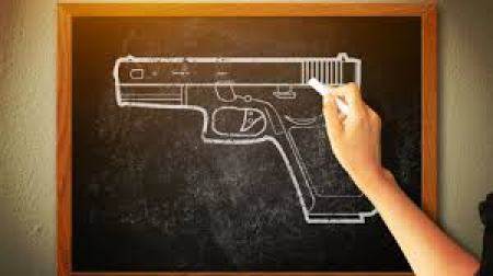 a chalkboard drawing of a gun with a student's hand holding the chalk