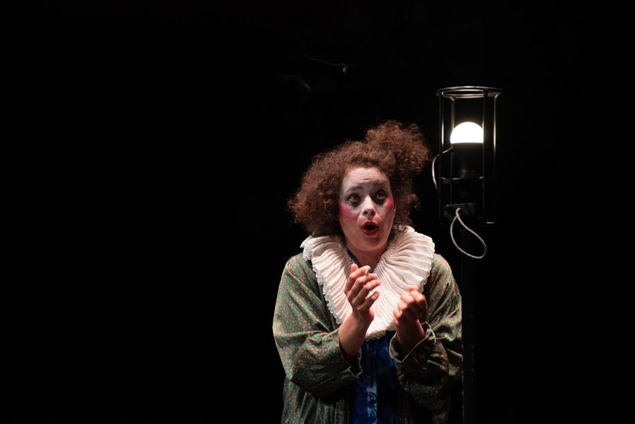 A woman dressed as a clown speaks to a street lamp.