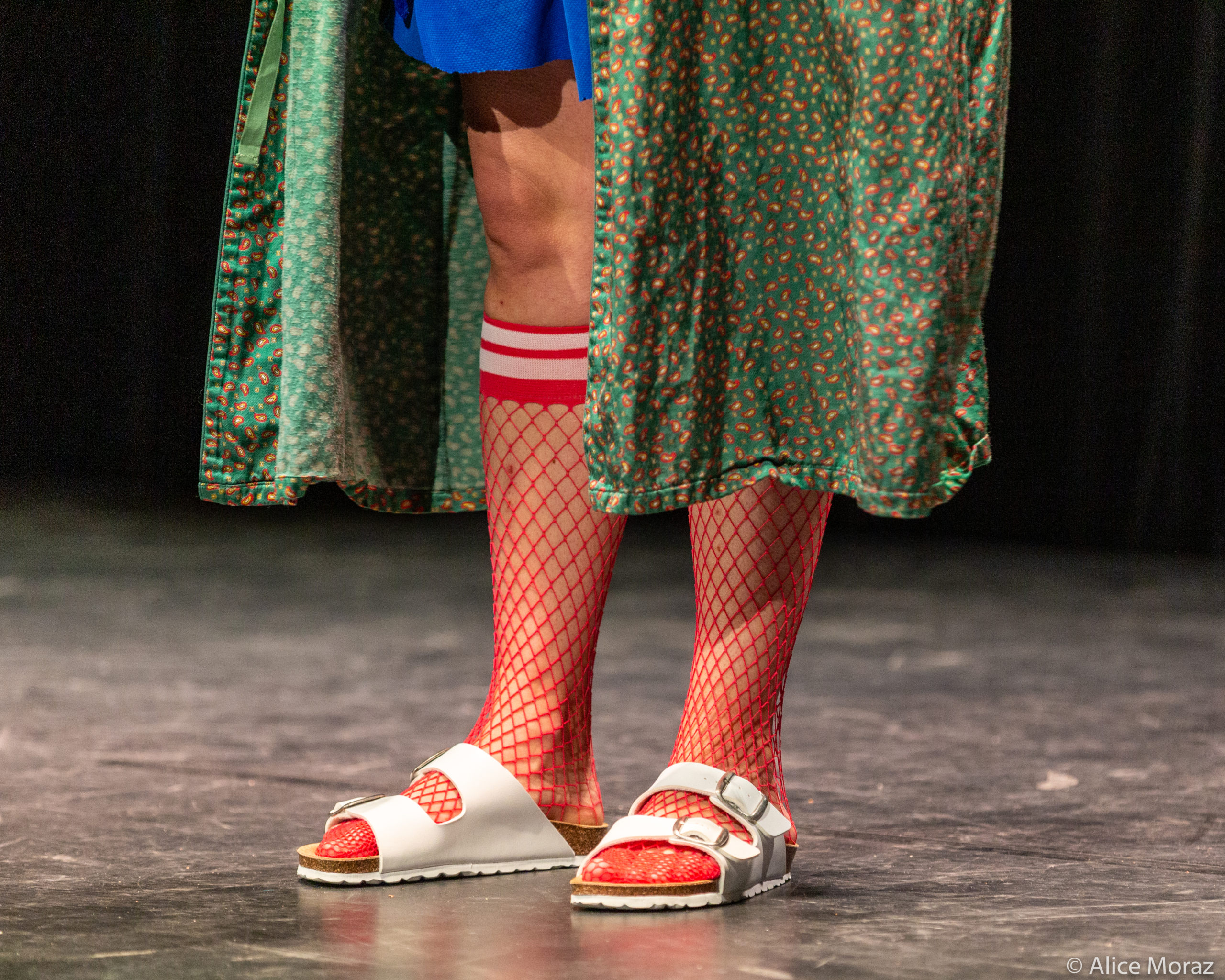 A pair of feet wearing Birkenstock sandals and mid-calf length bright red fishnets, as well as a green robe.