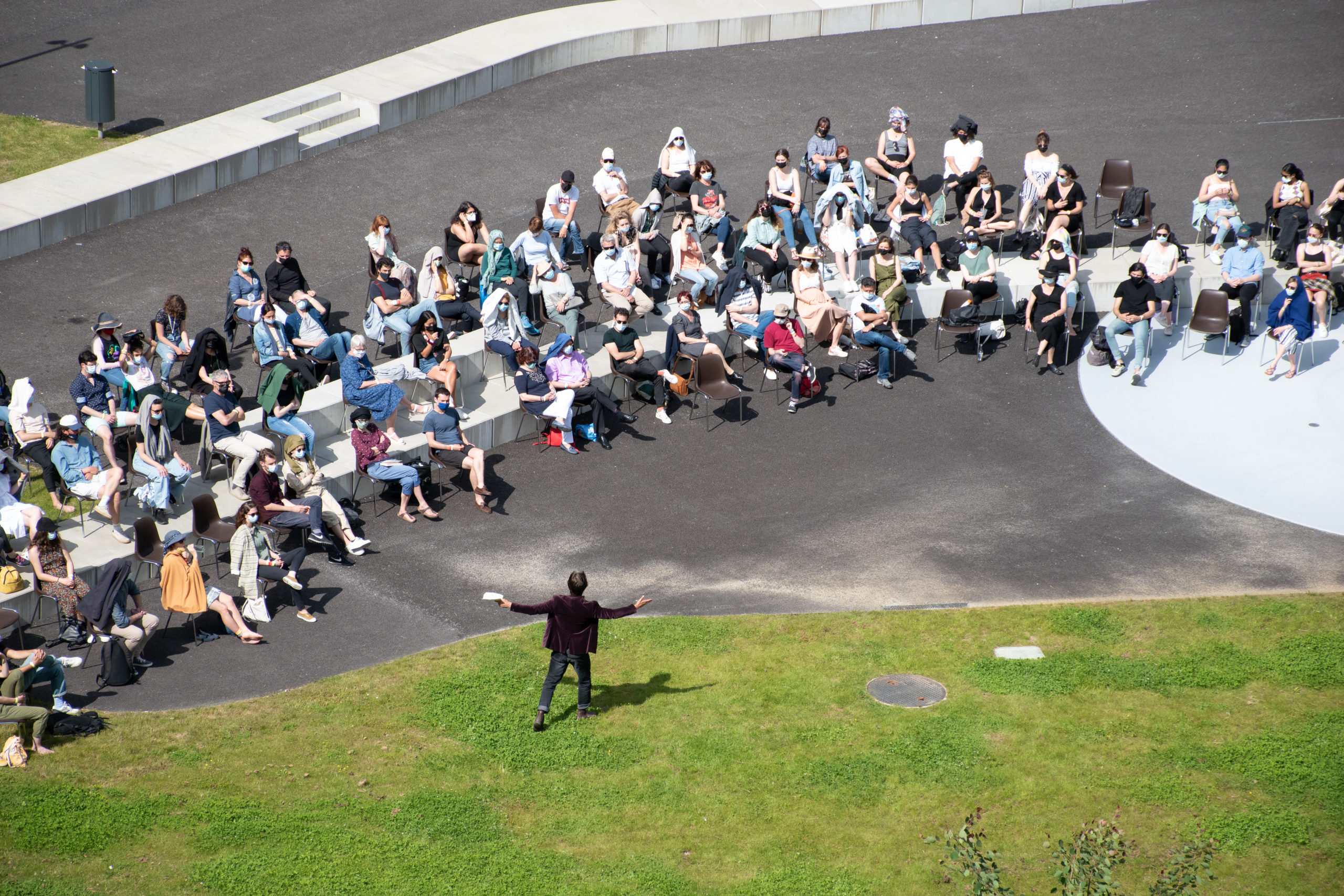 A man dressed in black is seen from above, performing in front of an outdoor audience.
