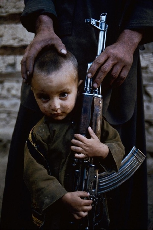 A young boy stands next to his father's AK-47. Kabul, Afghanistan, 1992