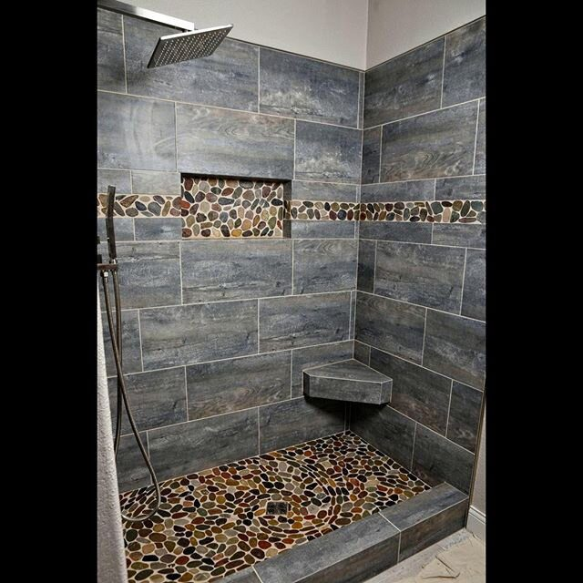 Master Shower Time 😍  A huge thank you to the Traverse family for trusting us with their master shower project. It was an absolute privilege.   Thank you to @diane_j_hochhalter_studio for taking these photos, sure beats our cell phones!   Pebbles were all laid one by one. Bench was custom made and all edges between tiles mitered. Sure beats the original acrylic surround.   Products used:  @emsertile Explorer *Paris* 12 x 24 Porcelain Tile @emsertile Rivera Pebbles @laticrete Spectralock Pro Epoxy Grout  @schlutersystemsna Kerdiboard & Rondec   #showerdesign #showergoals #showerroom #showersystem #interiordesign #design #bathroomdesign #homedecor #home #tileaddiction #tiles #tiledesign