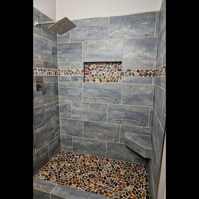 Master Shower Time ?⁠ ⁠ A huge thank you to the Traverse family for trusting us with their master shower project. It was an absolute privilege. ⁠ ⁠ Thank you to @diane_j_hochhalter_studio for taking these photos, sure beats our cell phones! ⁠ ⁠ Pebbles were all laid one by one. Bench was custom made and all edges between tiles mitered. Sure beats the original acrylic surround. ⁠ ⁠ Products used: ⁠ @emsertile Explorer *Paris* 12 x 24 Porcelain Tile⁠ @emsertile Rivera Pebbles⁠ @laticrete Spectralock Pro Epoxy Grout ⁠ @schlutersystemsna Kerdiboard & Rondec⁠ ⁠  #showerdesign #showergoals #showerroom #showersystem #interiordesign #design #bathroomdesign #homedecor #home #tileaddiction #tiles #tiledesign