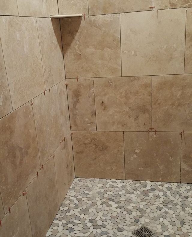 It's been a few years since we finished up this travertine/ pebble shower! 😍    #bathroom #ownthebathroom #bath #interiordesign #design #tiles #architecture #homedecor #decor #interior #interiors