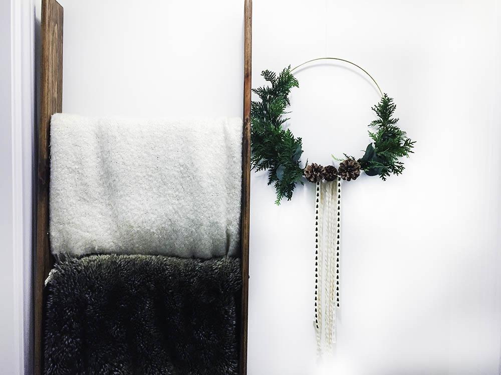 blankets on ladder beside winter wreath