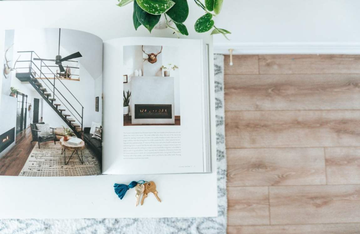 Homebody book on desk with set of keys and plant