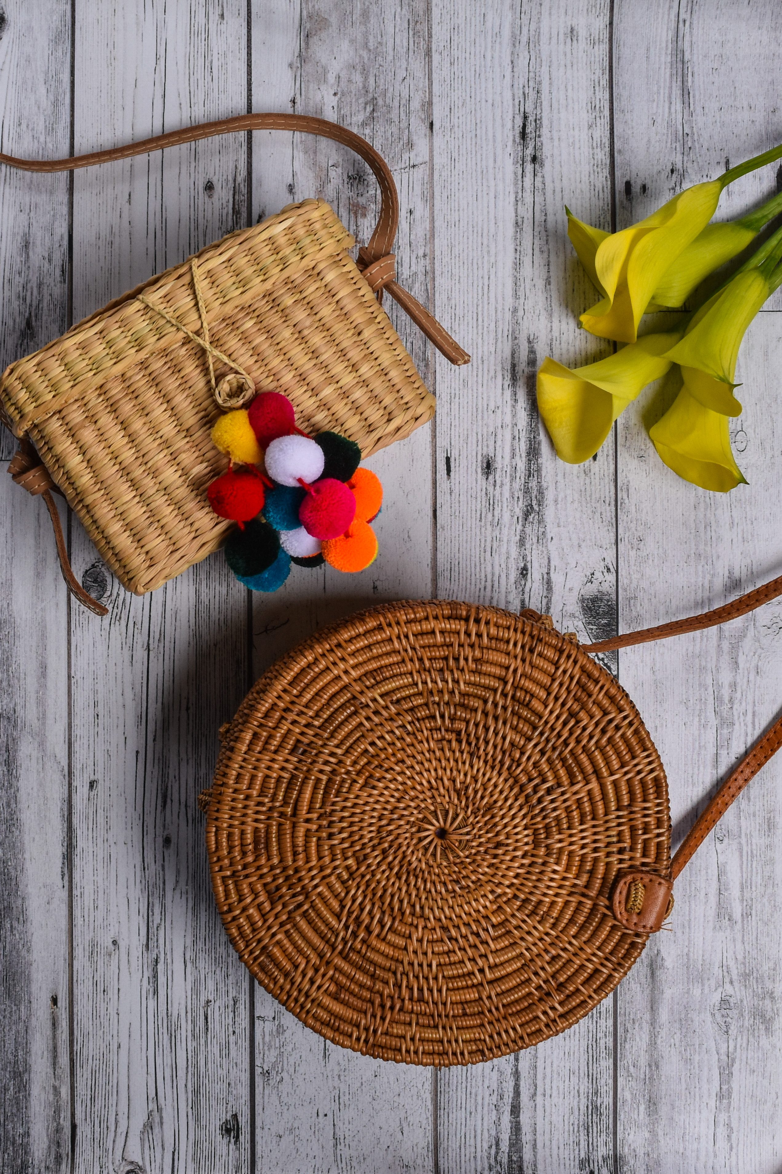 Rattan Round Straw Bag and Nannacay Baby Roge Pom Pom Straw Bags on wood table with yellow lilies