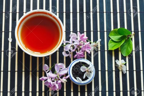 13590434-Cup-of-tea-jar-of-tea-leaves-and-cherry-blossoms-and-leaves-with-lilac-on-bamboo-table-cloth-still-l-Stock-Photo