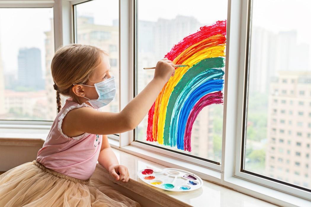 Niña en Cuarentena pintando arcoiris