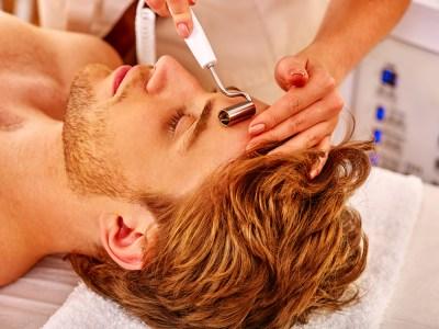 Young man receiving electric facial massage.