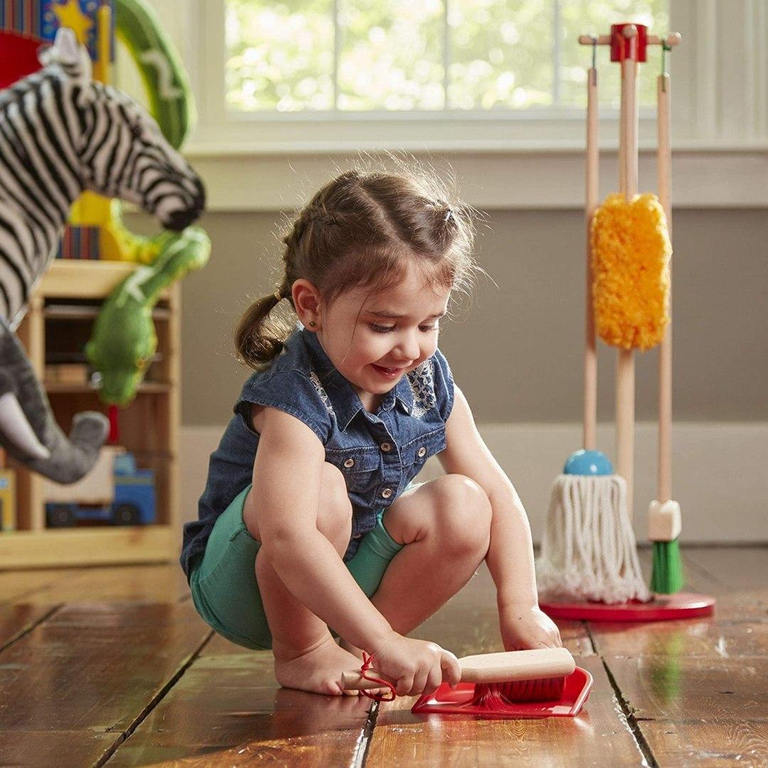 Petite fille qui ramasse des miettes avec la balayette et la pelle du kit de ménage Melissa et Doug