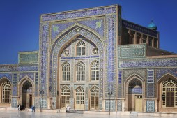 The walls are covered with colourful mosaic, surrounded by blue bands of Quranic script.